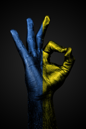 A hand with a drawn Ukraine flag shows an ok sign on a dark background. Vertical frame