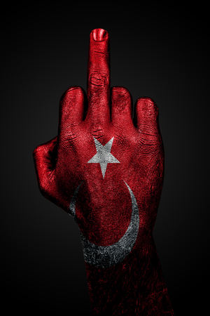 A hand with a painted flag of Turkey shows the middle finger, a sign of aggression, against a dark background. Vertical frame