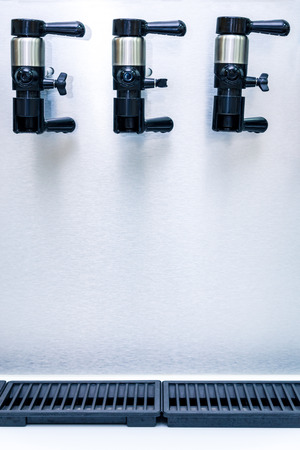 many modern faucets for pouring beer in a row
