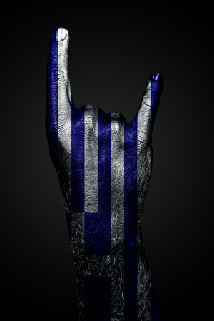 A hand with a drawn Greece flag shows a goat sign, a symbol of mainstream, metal and rock music, on a dark background. Vertical frame