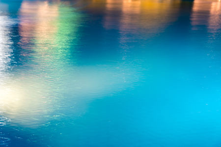 Abstract background, texture of blue water with multicolored highlights on it. Horizontal frame 版權商用圖片