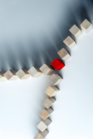 The long curved line of wooden cubes is divided into two after the red cubes, as a symbol of a queue, a competition for a position or a turning point, on an uneven white background Stock Photo