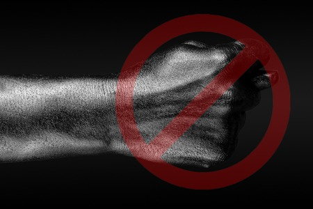 The red circle crosses out a hand that shows a fig, a sign of prohibition, disagreement, refusal, on a dark background. Horizontal frame