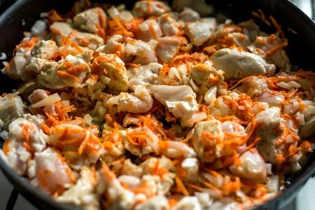 Cuisson, carottes tranchées et viande frite dans une poêle. Cadre horizontal Banque d'images