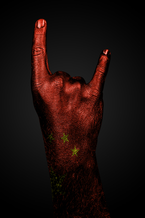 A hand with a drawn china flag shows a goat sign, a symbol of mainstream, metal and rock music, on a dark background. Vertical frame