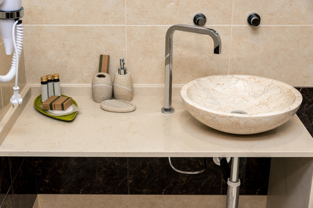 Modern bathroom, sink with faucet, soap and others. Horizontal frame Banco de Imagens
