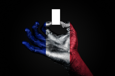 hand with a painted flag France holding a small white sheet with space for an inscription, mock up. Horizontal frame