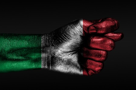 A hand with a painted Italy flag shows a fig, a sign of aggression, disagreement, a dispute on a dark background. Horizontal frame