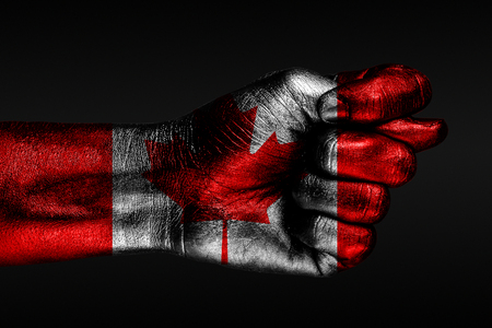 A hand with a painted Canada flag shows a fig, a sign of aggression, disagreement, a dispute on a dark background. Horizontal frame