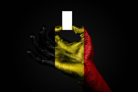 hand with a painted flag Belgium holding a small white sheet with space for an inscription, mock up. Horizontal frame 스톡 콘텐츠