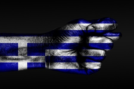 A hand with a painted Greece flag shows a fig on a dark background. Horizontal frame