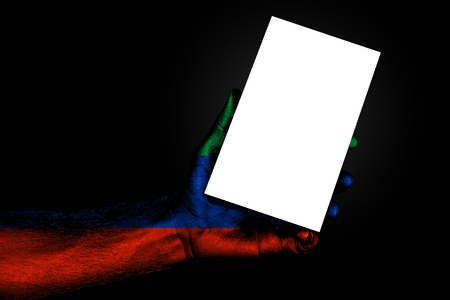 hand with painted flag Dagestan holding a large white sheet with space for an inscription, mock up. Horizontal frame 스톡 콘텐츠
