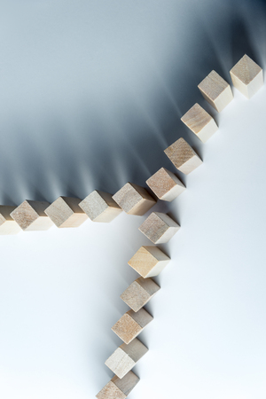 A long curved line of wooden cubes is divided into two, as a symbol of a queue, a competition for a position or a team, on an uneven white background. Stock Photo