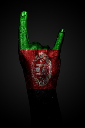 A hand with a drawn Afghanistan flag shows a goat sign, a symbol of mainstream, metal and rock music, on a dark background. Vertical frame