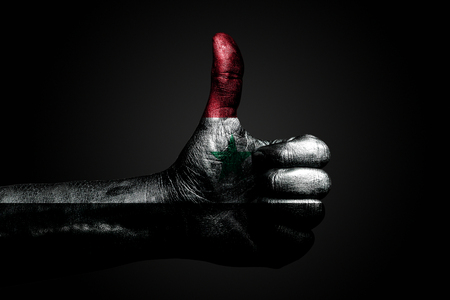 A hand with a drawn Syria flag shows a finger up sign, a symbol of success, readiness, a task done on a dark background. Vertical frame