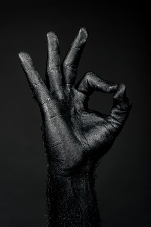 hand completely in black paint shows ok sign. Vertical frame