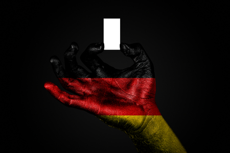 hand with a painted flag Germany holding a small white sheet with space for an inscription, mock up. Horizontal frame 版權商用圖片