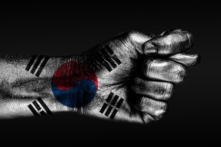 A hand with a painted South Korea,flag shows a fig, a sign of aggression, disagreement, a dispute on a dark background. Horizontal frame Stockfoto