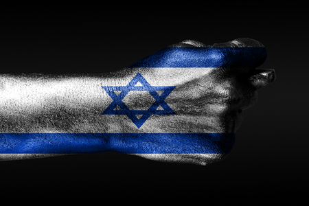 A hand with a painted Israel flag shows a fig, a sign of aggression, disagreement, a dispute on a dark background. Horizontal frame Stockfoto