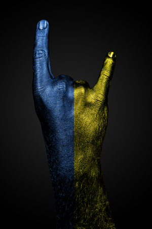 A hand with a drawn Ukraine flag shows a goat sign on a dark background. Vertical frame