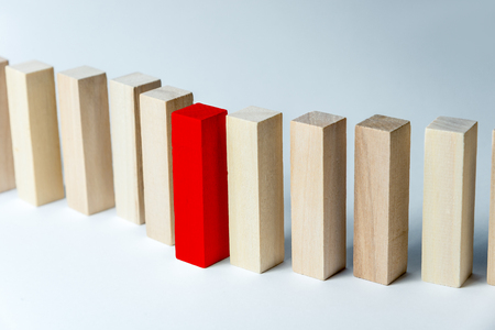 A long curved line of wooden cubes with one red, as a symbol of a queue, competition for a position or team, on a uneven white background Imagens