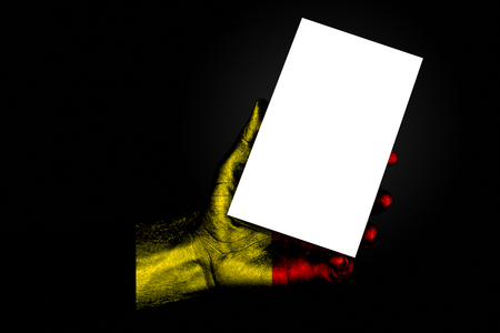 hand with painted flag Belgium holding a large white sheet with space for an inscription, mock up. Horizontal frame