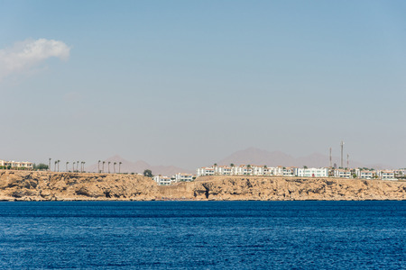 hotels and houses in the distance stand over a cliff above the blue sea. Horizontal frame