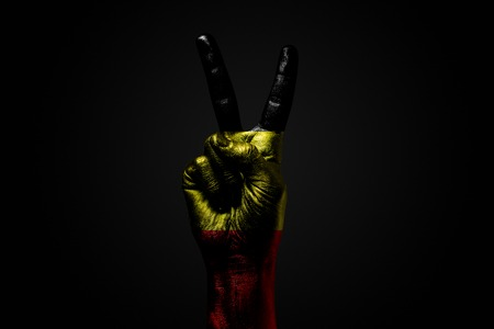 A hand with a drawn Belgium flag shows an PEACE sign, a symbol of peace, friendship, greetings and peacefulness on a dark background. Horizontal frame Imagens