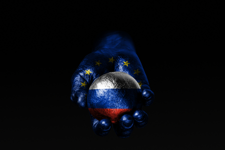 A hand with a drawn EU flag holds a ball with a drawn Russia flag, a sign of influence, pressure or conservation and protection. Horizontal frame