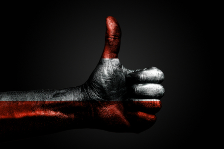 A hand with a drawn Austria flag shows a finger up sign, a symbol of success, readiness, a task done on a dark background. Vertical frame Banco de Imagens