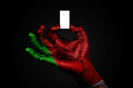 hand with a painted flag Belarus holding a small white sheet with space for an inscription, mock up. Horizontal frame