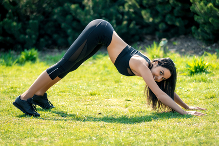 Slender beautiful girl with dark hair in sportswear is stretched in nature, a symbol of a healthy lifestyle, a strong personality and a desire for success and a sports body. Horizontal frame