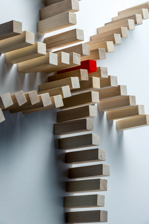 Many curved lines of wooden cubes are combined in the center into one red, as a symbol of queues, a variety of tasks and a leader, on an uneven white background