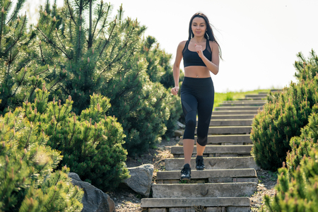 Slender beautiful girl with dark hair runs down the stairs, a symbol of healthy lifestyles, a strong leader and healthy competition. Horizontal frame Banque d'images
