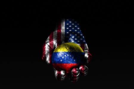 A hand with a drawn USA flag holds a ball with a drawn Venezuela flag, a sign of influence, pressure or conservation and protection. Horizontal frame