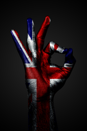 A hand with the painted flag of UK shows an OK sign on a dark background. Vertical frame