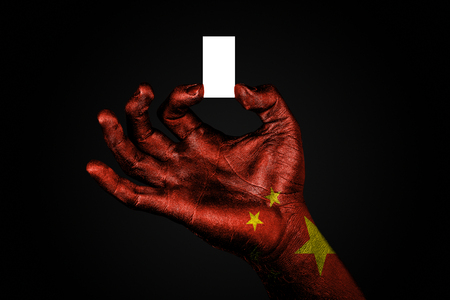hand with a painted flag China holding a small white sheet with space for an inscription, mock up. Horizontal frame