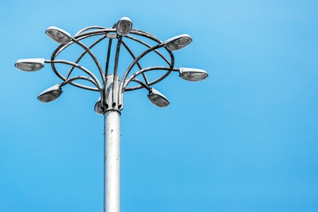 Tall old city lamppost stands against blue sky. Horizontal frame