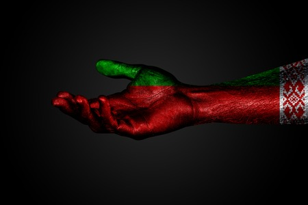 An outstretched hand with a painted flag of Belarus, a help sign or a request, on a dark background. Horizontal frame
