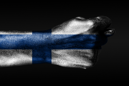 A hand with a painted Finland flag shows a fig, a sign of aggression, disagreement, a dispute on a dark background. Horizontal frame