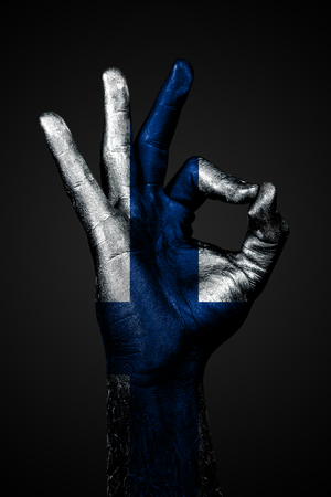 A hand with the painted flag of Finland shows an OK sign on a dark background. Vertical frame