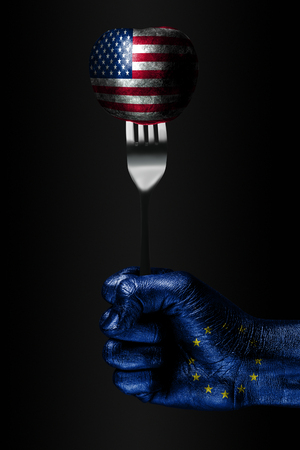 A hand with a drawn EU flag holds a fork, on which is a ball with a drawn USA flag, a sign of influence, pressure, grip and anecxia. Vertical frame