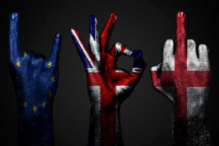 a set of three hands with a painted flag of England, United Kingdom and European Union show middle finger, goat and Okay, a sign of aggression, protest and approval on a dark background. Horizontal frame