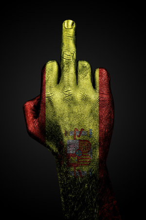 A hand with a painted flag of Spain shows the middle finger, a sign of aggression, against a dark background. Vertical frame