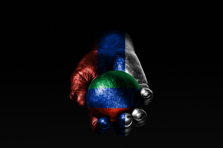 A hand with a drawn Russia flag holds a ball with a drawn Dagestan flag, a sign of influence, pressure or conservation and protection. Horizontal frame