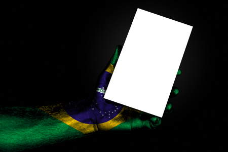 hand with painted flag Brazil holding a large white sheet with space for an inscription, mock up. Horizontal frame