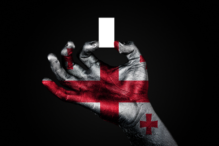 hand with a painted flag Georgia holding a small white sheet with space for an inscription, mock up. Horizontal frame