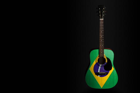 Acoustic concert guitar with a drawn flag Brazil, on a dark background, as a symbol of national creativity or folk song. Horizontal frame