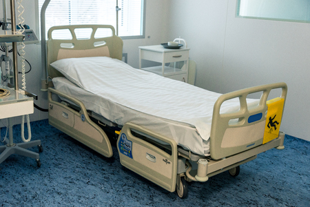 interior in a hospital, hospital bed with additional shelves and equipment in the room. Horizontal frame