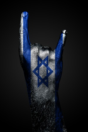 A hand with a drawn Israel flag shows a goat sign, a symbol of mainstream, metal and rock music, on a dark background. Vertical frame